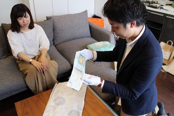 白大島紬の証紙を確認する査定員
