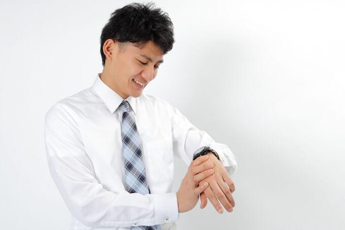 腕時計をつける男性